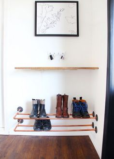 Simple entryway with copper shoe rack and faux barn board shelf. Modern farmhouse on the cheap. Love the new vinyl plank floors -- they look like real hardwood!