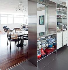 Ao eliminar a parede inteira entre a cozinha e a sala, ganhou-se espaço para criar a sala de jantar. De aparência moderna e funcional, o aço inoxidável está no armário que separa os ambientes, com nichos vazados. Projeto do escritório AMZ Arquitetos