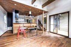 深みのあるウォルナット材の床に板張り風の天井。アイアンの黒をキリリと効かせた、ブルックリンテイストのLDK。キッチンのカウンターも木×黒でシンプルに仕上げ、天井からの吊り棚を収納兼空間のアクセントに。キッチン奥の洗面室にはあえて扉をつけず、ブルーの壁を差し色にしている。階段はLDK内に設けた子育てファミリーに適したプランです。