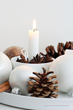 Pine cones, cinnamon sticks, candles and ornaments on a tray. Simple winter/christmas decor.