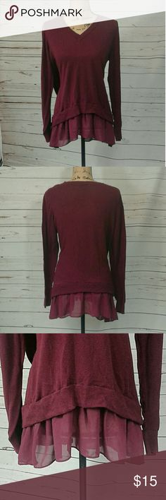 Torrid blouse V neck Long sleeve wine colored top.  ruffle hem. Super cute! 63% cotton, 37% rayon. Trim at bottom is 100 % polyester.  Has a bit of stretch. Some pilling. Armpit to armpit measures 22 inches. Shoulder to hem is 25 inches including trim which is 4 1/2 inches. torrid Tops
