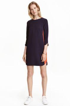 Vestido curto: Vestido curto em tecido. Modelo de corte direito com mangas a 3/4 com pequena racha na extremidade, abertura e botão na parte de trás do pescoço e base arredondada. Sem forro.