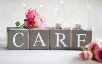 Rosarote Rosenknospen und Teelichter auf Pappwürfeln mit Typoprint 'CARE'