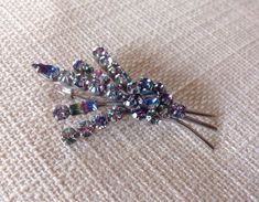 A personal favourite from my Etsy shop https://www.etsy.com/uk/listing/398998271/1950s-rainbow-diamante-brooch-just