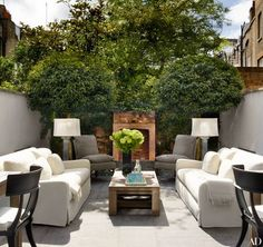 Flanking the rear garden's fireplace at a London townhouse renovated by Philip Vergeylen are chairs clad in a Manuel Canovas cotton; the cocktail table and sofas are by RH, the latter dressed in a Perennials fabric | archdigest.com