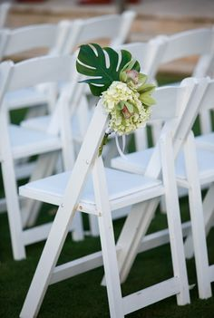 CD Florals Real Wedding: Mary Beth & John – Part II Photo credit: http://kate-belle.com Tropical aisle marker made of Monstera Leaf, white Hydrangea and lime Cymbidium Orchids on a white garden chair.
