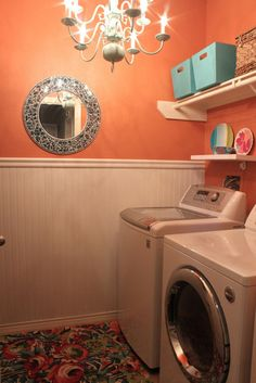How about doing laundry in style...chandlier adds a touch of class to this laundry room, small shelf for displaying a bit of color and design, the mirror adds dimension and gives visual appeal...lovely paint and wainscoating, too.