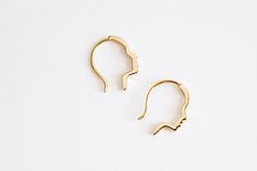 <p>These earrings are more than just a coupla pretty faces (though make no mistake—they are very much that). From far away, they look like glinting golden hoops, but if you wanna invite someone to get, well, all up in your mug, they'll catch sight of those low-profile profiles.</p>