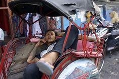 Conductor d'un #becak dormint a un carrer de #Yogyakarta, a l'illa de #Java, a #Indonèsia.