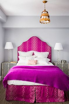 Fabulous bedroom features gray walls framing a hot pink print headboard with matching bedskirt on full bed dressed in fuchsia blanket and pink damask pillow flanked by black and white striped cabinets used as nightstands topped with crystal table lamps illuminated by gold leaves chandelier.