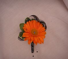 Boutonniere is made with an orange gerber daisy with bling in the middle, also has grennery and is wrapped in a black and silver ribbon.
