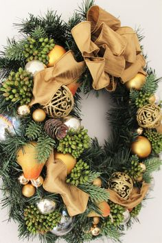 Christmas wreath with gold ribbon.  Using gold, clear color ornaments, pine cones. green berries, and pears.  It measures approx. 19 diameter.