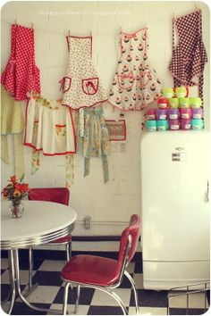 Vintage aprons hung on indoor clothesline along the wall. :)