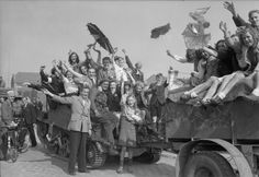 Cheering Dutch civilians swarm onto a universal carrier and trailer as Eindhoven is liberated, 19 September 1944.