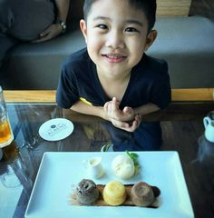 """What could be more happy during afternoon time ? Of course our """"Afternoon Tea Package"""" is the answer. like this happy child wanted to finish these dessert.  #on20makassar 
