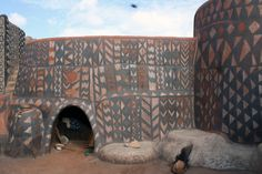 WithinBurkina Faso, West Africais a circular 3 acre complex of intricately embellished earthen architecture known as the village of Tiebele. It is here that the community enlivens the earthen walls of their village by annually adorning them with traditional African patterns. To them