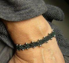 Ein geknüpftes **Armband** in Waldgrün mit eingearbeiteten silberfarbenen Perlchen.  Es ist größenverstellbar und lässt sich somit individuell anpassen. Material: S-Lon Cord (Nylon)