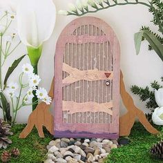 A Fairy Door ~What you'll need:   *Fairy Door template  *Tree rot door stand template  *Scissors  *Pencil  *Thin cardboard  *Scrapbook paper (brown or wood grain) for the cross boards  *Corrugated cardboard  *Glue stick  *Stud-style pierced earring or button for the doorknob  *Pebbles or small stones  *Silk flowers and greenery