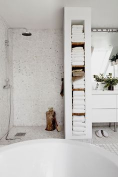 Small tiles in a white bathroom, with store space built in to the walls / dividers.