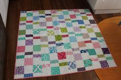 """This perfect little baby quilt is so simple yet so sweet. The print fabrics in the quilt top are from the LOL collection by Moda Fabrics.  This quilt measures 50"""" x 52"""". It is going to be beautiful in the nursery or perfect for use in the carseat or stroller. The quilt is backed in fun print fabric with colors pulled from the top. The quilt is quilted in a big floral design in a white cotton thread."""
