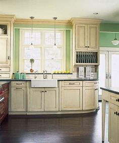 Neutral semi-custom Merillat cabinets leave room for a more eye-catching wall color, like this summery green. | Photo: Courtesy of Merillat