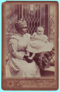 A cabinet card portrait of a beautiful black nurse with her white charge. The young woman is dressed in European dress, with a Mother Hubbard apron and a head-wrap.   An inked inscription in a period hand recto in the lower margin reads: 'Baby Merle / 6 months & 3 weeks / April 1903.'