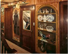 A CURIO CABINET OF DECORATIVE OBJECTS, A HANGING COAT, HAT, SHOES, clock, HANGING PLANT AND BOOK SHELVES ADD A LOT OF EXCITEMENT, AS WELL AS THE ILLUSION OF 3-D DEPTH TO A WALL, THAT IS TOO SMALL, AND IN A HALLWAY TOO NARROW TO FIT FURNITURE.