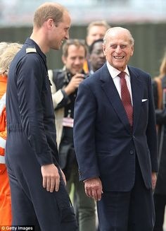 July 13, 2016: Prince William and his grandfather the Duke of Edinburgh grin at each other at Prince William's place of work - the East Anglia Air Ambulance Base at Cambridge. ~ Photo by Getty Images.