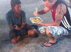 A tourist helps to feed a homeless amputee