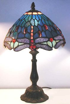 One of the most popular of these patterns through the years has been the dragonfly design. The dragonfly appears to be suspended, and its head and wings form the lower edge of the lamp shade. They were originally created in shades of blue and green, but these days you will find Tiffany style lamps that feature dragonflies in colors to match any decor.