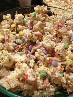 Bunny Bait!!! 2 cups pretzels, 1 bag popped white popcorn, 1 package almond bark white melting chocolate, 1 bag of festive M, 2 cups of chex cereal, 1 container of sprinkels. Spread pretzels, popcorn and chex on a foik covered baking sheet and drizzle white chocolate over the mixture...gently stir to coat evenly...add sprinkles but dont stir it anymore or the sprinkles will be coated with chocolate and turn white...let harden on cookie sheets and then break apart and add M to the finished mixture.
