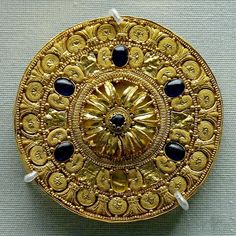 Ear-stud decorated with a rosette surrounded by concentric bands. Gold with vitreous glass paste insets, Etruscan artwork, 530–480 BC.   British Museum