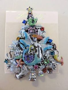 "KIRKS FOLLY MERMAID MAGIC PIN/ PENDANT = 3"" TALL AND IS 2 1/2"" WIDE. OUR MERMAIDS ARE SURROUNDED BY ANIMALS OF THE SEA. THERE ARE CRYSTAL BEADS, SHIPS WHEEL, STARFISH, BEAUTIFUL DIFFERENT COLOR STONES, DOLPHINS AND MORE. Z"