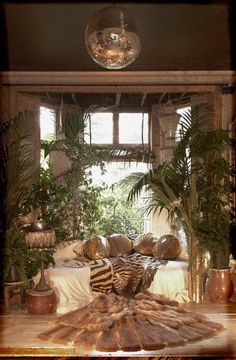 Luxe boho living space. Gorgeous fur, animal prints, lush greenery, vintage lamp and that disco ball!