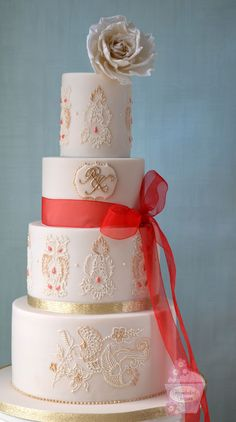 Wedding cake topped with a sugar rose and decorated with lace brush embroidery inspired by bride's very sparkly red wedding dress. Hand piped monogram and piping on the bottom tier inspired by the invitations.