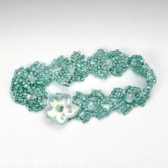 This lovely bracelet has seafoam green lined triangular glass seed beads that are woven in a modification of Ecuadorian weave that I worked out to make a flower-like pattern. Each flower has a Swarovski crystal round bead in the center. The closure consists of a seed bead loop and a large glass flower bead that coordinates with the crystal beads. This is one bracelet that you will actually want the clasp to show.  This bracelet is about 7.5 (~19 cm) in length and 3/4 wide (19 mm) and wil...