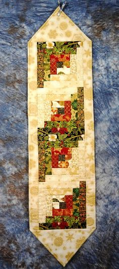 This beautiful, quilted table runner contains four log cabin quilt blocks composed from gorgeous Holiday fabrics. Backing for the runner is poinsettias on black making the runner reversible and appropriate for use throughout the winter and holiday season. It is machine pieced and