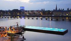 """Badeschiff – Berlim, Alemanha  Em alemão, Badeschiff significa literalmente """"navio de banhos"""", nome mais do que apropriado para esta piscina pública que flutua no Rio Spree, ao largo do centro da cidade de Berlim. Uma embarcação de fundo achatado foi reaproveitada para criar esta piscina com mais de 27 metros que no Verão é complementada por um café sobre um deck de madeira flutuante e uma praia artificial; e no Inverno por uma cobertura e várias saunas."""