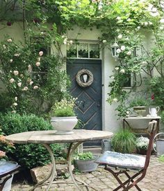 The focal point of this picture is the wreath on the door because it is white ag. - The focal point of this picture is the wreath on the door because it is white against a solid grey - Cottage Patio, Cottage Garden Design, Cottage Garden Plants, Garden Spaces, Country Cottage Garden, Small Gardens, Outdoor Gardens, Front Yard Landscaping, Landscaping Ideas