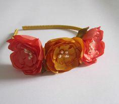 Tiara forrada com fita de cetim, com três flores de cetim estilo hibiscus em tom mostarda e laranja fechado. O tamanho da tiara serve tanto para crianças quanto adultas. diâmetro das flores: 4,5 cm cada (ver foto)