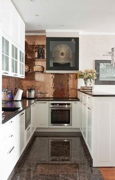 tiny copper tiles, marble floors and white cabinets