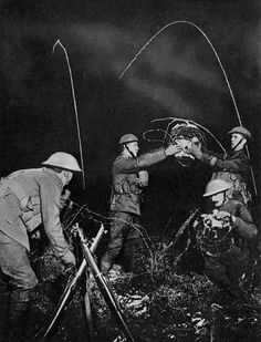 WW1, 1916. British soldiers erecting barbed wire entanglements in No Man's Land at night Star shell flares seen behind.