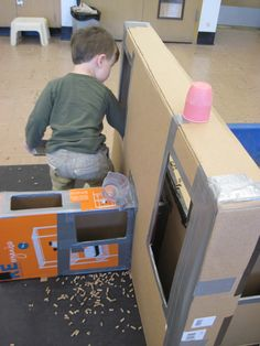 The great thing about using cardboard boxes as containers next to the sensory table is that they come in all shapes and sizes.  This tall, skinny box offers a much different experience for transporting the medium than a large, open box.  Imagine how this child is experiencing space as he is reaching through the hole to retrieve some pellets.