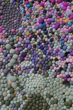 Chilean artistSerena Garcia Dalla Venezia creates stunning textile art from small handmade fabric balls that she then groups together.