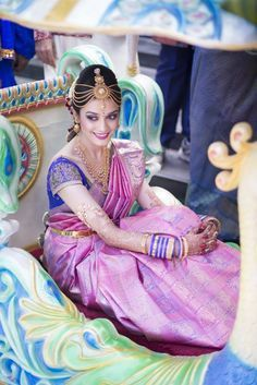 Traditional Southern Indian bride wearing bridal silk saree, jewellery and hairstyle. Maang Tikka. Temple jewelry. Jhumkis. Silk kanchipuram sari. Braid with fresh flowers.