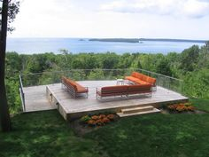 Set above the tree line, this clear deck railing designed by Pureview Railings provides safety without being distracting. This standalone platform features plush seating and plenty of room to relax and enjoy the calming water elements.