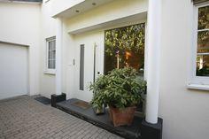 Hauseingangstüre in moderner, schlichter Optik.   Türe beidseitig flächenbündig gearbeitet mit verdeckten Türbändern und flächenbündig eingelassenen Beschlägen in Verbindung mit modernster Sicherheitstechnik.