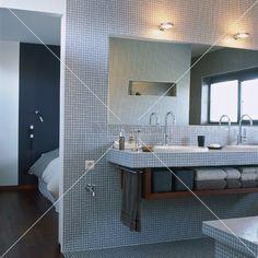living4media - mit blauen mosaikfliesen gefliestes badezimmer mit gemauertem waschtisch und blick in den schlafraum