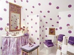 Coordinating fabric and wall treatments are a convenient way to make a bath come together. Scenic toile paired with large lavender painted circles on stark white creates a lively, youthful look in this bath. The gathered skirt around the sink is an inexpensive way to hide plumbing and provide a perfect storage area. Other budget-friendly ideas to try: Accent the bathroom using inexpensive artwork, lamps, and small porcelain plates. Reupholster an old stool to add seating.