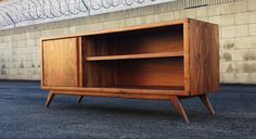 Mid century modern inspired credenza. This will make a statement in any room. Made out of solid and domestic furniture grade walnut ply. It has one